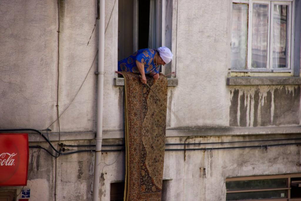 Senhora turca limpando seu tapete na janela