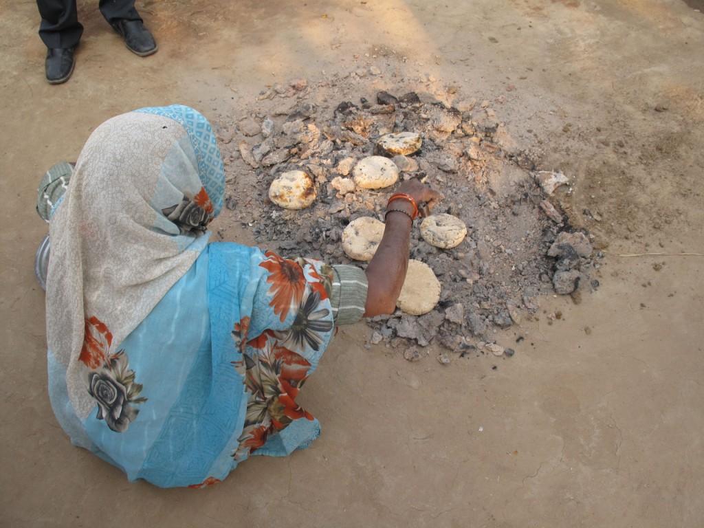 Mulher cozinhando o pão na braza do esterco