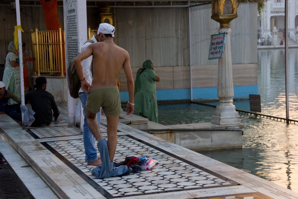 Homem se banhando na piscina sagrada do Golden Temple
